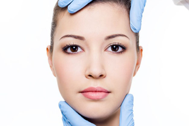 mani del dottore sulla faccia per chirurgia del viso