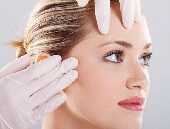 donna con mani del dottore che toccano la sua faccia