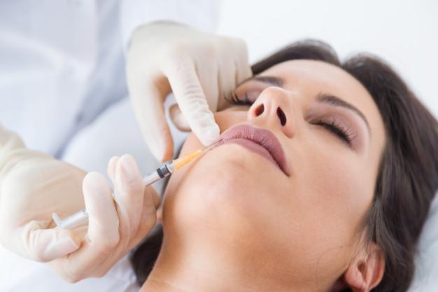 dottore inietta filler di acido iauloronico sulle labbra